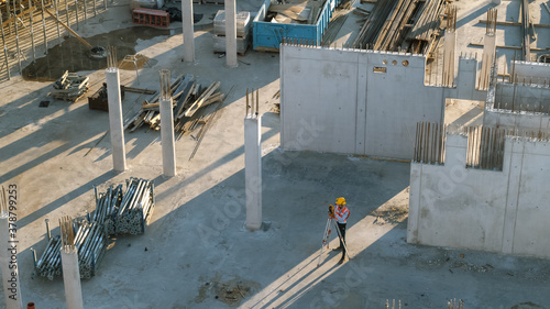 Photo Aerial Shot of a Construction Worker Using Theodolite Surveying Optical Instrument for Measuring Angles on Construction Site