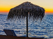 Seascape At Dawn. Isolated.Silhouette Of Straw Umbrella And Deckchair On Beach On A Greek Island At Sunset. Seascape Photography. Stock Image.