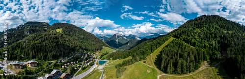 Fototapeta Panoramic view of alpine meadows and rocks in sunset evening lighting