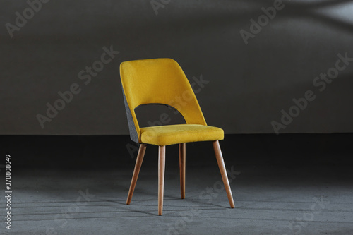 Fototapeta Modern yellow chair with wooden legs in a room under the lights