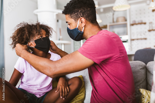 Fotografia Father in a medical mask puts a protective mask on his daughter at home