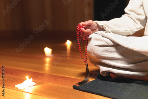 Foto Close-up of a male monk's hand holding a red wooden rosary in a dark practice room against a background of candles and a wooden floor