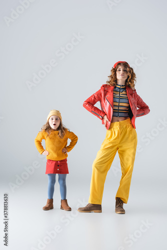 Fototapeta mother and daughter in colorful red and yellow outfits posing with hands on hips on grey background obraz