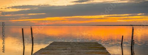 Fotografie, Obraz Ponton pour la pêche au bord d'un étang en Camargue dans le sud de la France au coucher du soleil