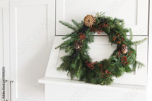 Fototapeta Rustic christmas wreath hanging on modern kitchen hood, festive holiday decoration. obraz