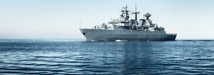 Large grey modern warship sailing in still water. Clear blue sky. Baltic sea, Germany. Global communications, international security theme. Panoramic image