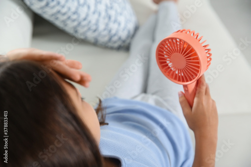 Fototapeta Little girl with portable fan suffering from heat at home. Summer season obraz