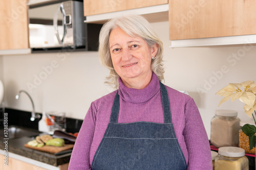 Obraz na plátně Lovely Senior grandmother with cooking apron smiling in camera at kitchen table, inside