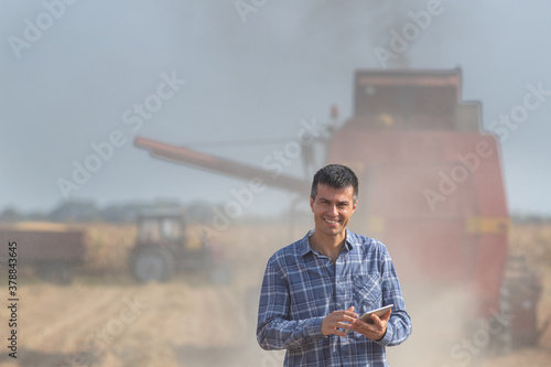 Fototapeta Farmer with tablet in front of combine harvester in soybean field obraz