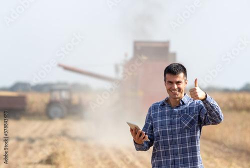 Fototapeta Farmer with tablet in front of combine harvester in soybean field obraz