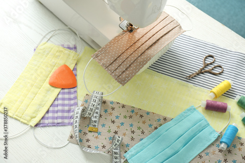 Sewing machine, craft accessories and cloth masks on white wooden table Canvas