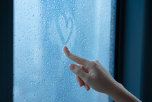 Female Hand Drawings A Heart On A Foggy Window During The Rain. Glass In Drops Of Water. The Concept Of Romance.