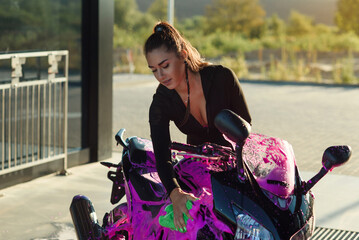 Beautiful girl in tight-fitting seductive suit washes black sport motorcycle and wipes it from magenta foam at sunrise.