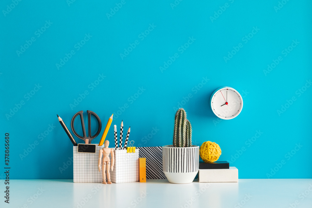 Fototapeta Desk with a blank picture frame or poster, school objects, office supplies, books, and plant on a blue background.