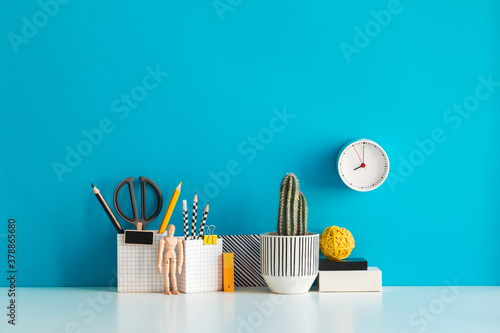 Desk with a blank picture frame or poster, school objects, office supplies, books, and plant on a blue background.