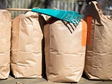 A Green Leaf Rake Lying On A Row Of Full Kraft Paper Leaf Bags In The Fall