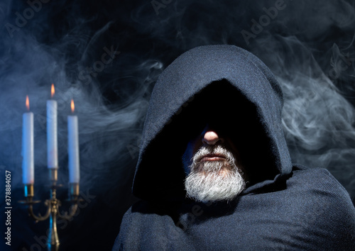 Fotografie, Obraz Portrait of a hooded man against a dark background with a candlestick