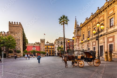 Fototapeta Seville, Spain. October 15th, 2020. Horse-drawn carriage waiting for tourists in Calle Miguel Mañara near the Porta del Leon, entrance to the Alcazar of Seville. obraz