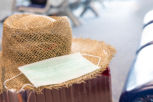 Obraz Defocus focus and blurred shot of surgical face mask, together with straw hat and travel luggage inside waiting seat area of Airport terminal. New normal lifestyle for traveler after Coronavirus. - fototapety do salonu