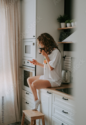Young pretty woman drinks coffee sitting at her kitchen at home and using smartphone enjoys of morning. Smiling woman reading phone message. #378903848