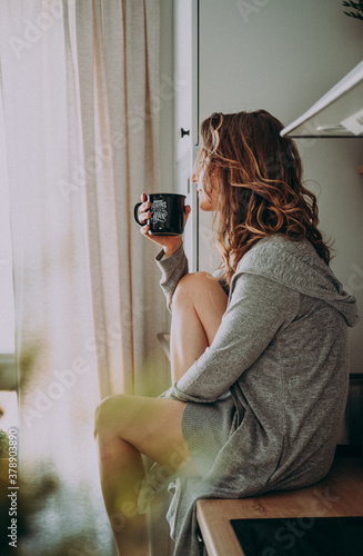 Young pretty woman drinks coffee sitting at her kitchen at home and looking out the window enjoys of morning. #378903890