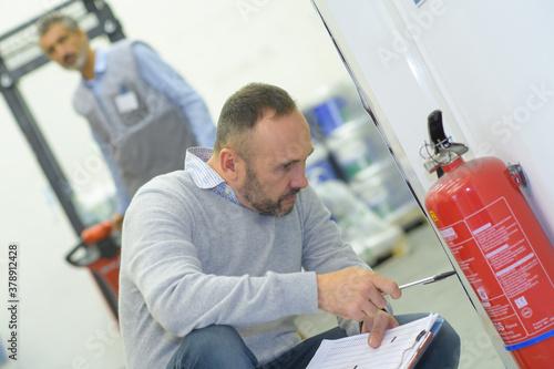Fototapeta a professional checking fire extinguisher