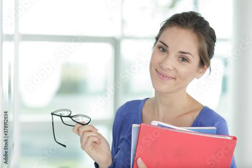 Fototapeta portrait of secretary holding files and her eyeglasses obraz