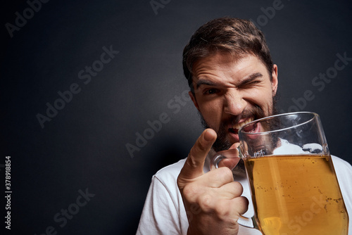 Fotografering man with a mug of beer in a white t-shirt emotions lifestyle drunk on a dark iso