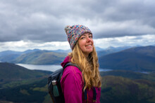 Woman Smiling And Happy While Hiking Ben Nevis Mountain, Scotland, UK With A Winter Hat And A Beautiful Backdrop Of Mountains And Lakes