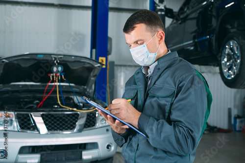 mechanic maintaining car record on clipboard at the repair shop.