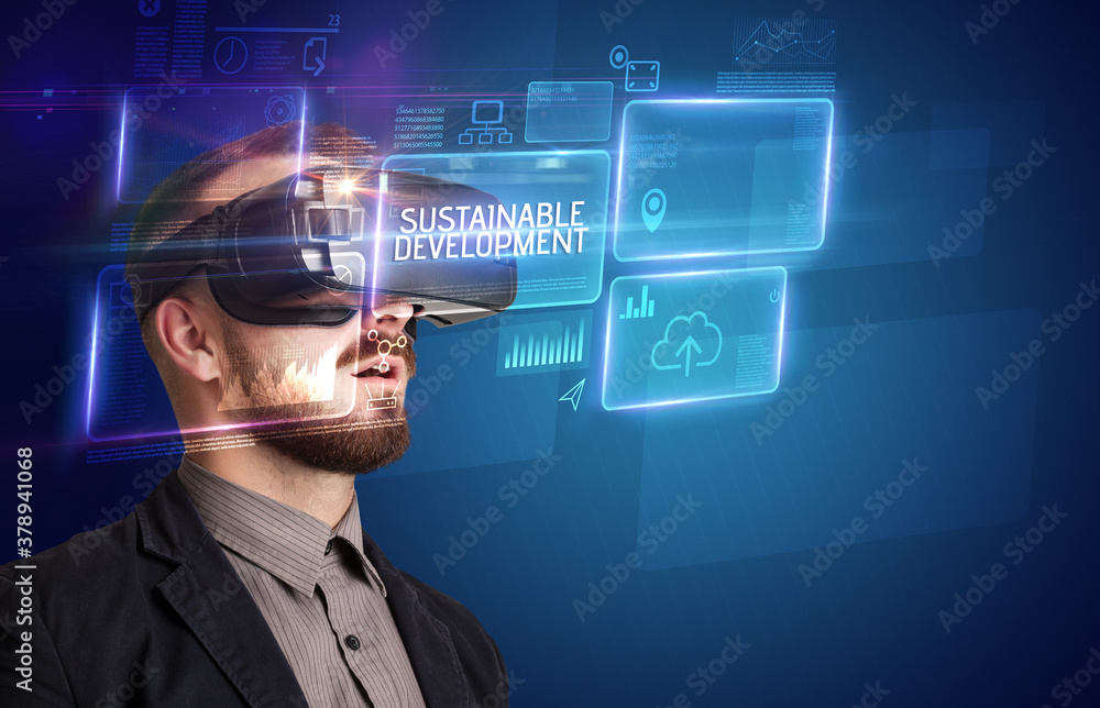 Fototapeta Businessman looking through Virtual Reality glasses with SUSTAINABLE DEVELOPMENT inscription, new technology concept