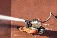 French Firefighter In Helmet With Fire Hose Shot With Top-down View