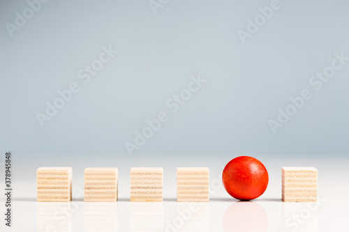 Be Different in a Row, wooden red ball in wooden cubes