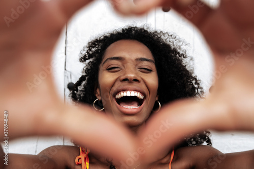 Foto Cheerful ethnic woman with heart gesture