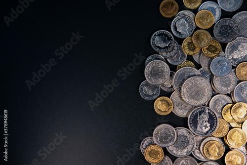 Obraz na plátne Swiss franc coins lie on a dark background.