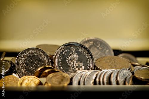 Fototapeta Swiss franc coins lie on a light background.