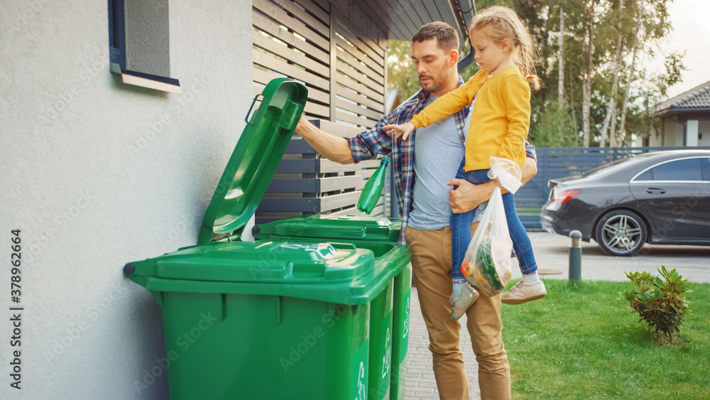 Fototapeta Father Holding a Young Girl and Throw Away an Empty Bottle and Food Waste into the Trash. They Use Correct Garbage Bins Because This Family is Sorting Waste and Helping the Environment.