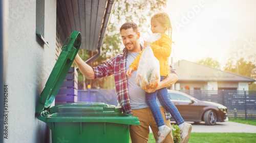 Father Holding a Young Girl and Throwing Away a Food Waste into the Trash. They Use Correct Garbage Bins Because This Family is Sorting Waste and Helping the Environment.