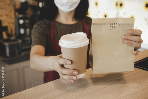 waitress wearing protection face holding hot coffee cup and paper bag waiting fo Canvas