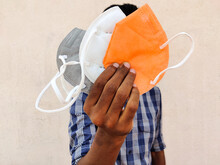 South Indian Man Showing Three KN-95 Face Masks In White,grey And Orange Color. Isolated On White Background.