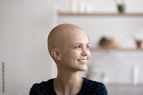 Obraz na plátně Close up of happy young Caucasian sick hairless woman suffering from oncology look in distance dream or visualize of recovery