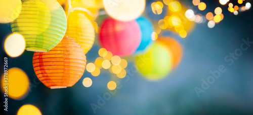 Fototapeta Festive background with colorful lights garland and bright bokeh. Holiday light decor. Celebration concept. obraz