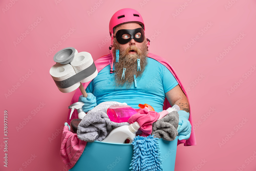 Fototapeta Shocked bearded plump man janitor in superhero costume looks after children and does cleaning at same time poses with basin full of laundry detergents looks surprisingly aside. Household concept