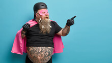 Shocked Superhero Points At Blank Space Wears Pink Mantel And Mask Shows Something Astonishing Isolated Over Blue Background Wears Clothespins On Thick Beard. Man In Costume Shows Blank Space.