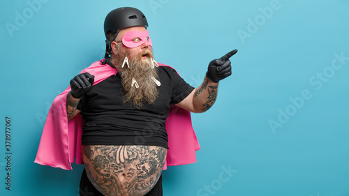 Fényképezés Shocked superhero points at blank space wears pink mantel and mask shows something astonishing isolated over blue background wears clothespins on thick beard