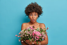 Horizontal Shot Of Scared Dark Skinned Woman With Curly Hair Stares At Camera Keeps Big Nice Festive Bouquet Of Flowers Over Naked Body Isolated On Blue Background. Womens Day Spring Time Concept