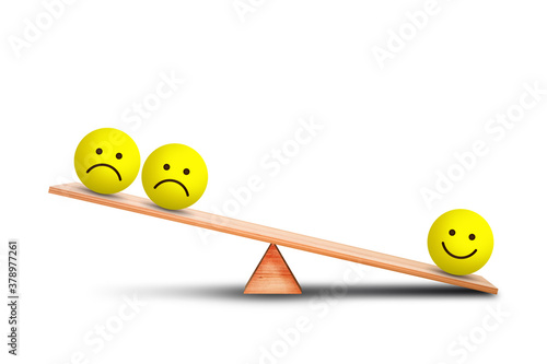 Photo Emotional and Customer Feedback Concept : Smiles emotional icon symbol outweigh more than sad emotional icon symbol on wooden balance scales with white background