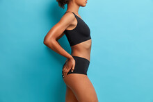 Sexual Slim Woman Stands In Profile Wears Black Sport Clothes Poses Against Blue Background. Attractive Slender Female Demonstrates Her Perfect Body. Wellness Concept