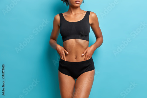 Obraz Sporty dark skinned woman demonstrates results after fitness training dressed in black cropped top and panties cares about body isolated on blue background - fototapety do salonu