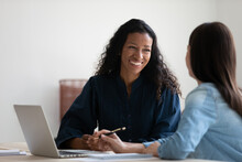 Smiling African American Businesswoman Talking To Colleague, Diverse Employees Brainstorming, Sitting At Table In Office, Manager Consulting Client, Using Laptop, Mentor Coach Training Intern